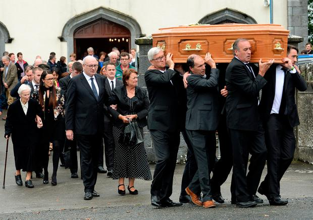 Phil Hogan and family walk behind his mother's coffin as it is carried from the church. Photo: Caroline Quinn