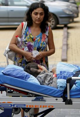Ashya King, a 5-year-old British boy with a brain tumour, lies on a stretcher as he arrives with his mother Naghemeh King at the Proton Therapy Center in Prague September 9, 2014. REUTERS/David W Cerny