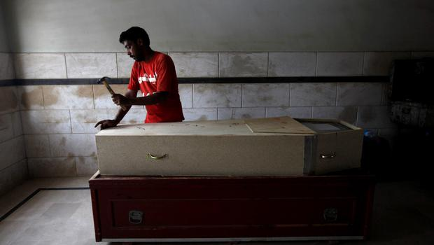 A volunteer prepares a coffin of a deceased who died due to an intense heat wave, before handing over to relatives, at Edhi Foundation morgue in Karachi, Pakistan, June 22, 2015. An intense heat wave killed more than 120 people over the weekend in Pakistan's southern city of Karachi, officials said on Monday, as the electricity grid crashed during the first days of the Muslim holy month of Ramadan. REUTERS/Akhtar Soomro