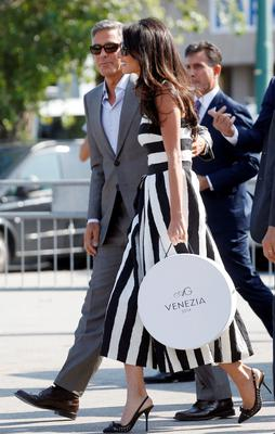 George Clooney, left, and his fiancee Amal Alamuddin arrive in Venice, Italy, Friday, Sept. 26, 2014. Clooney, 53, and Alamuddin, 36, are expected to get married this weekend in Venice, one of the worlds most romantic settings. (AP Photo/Luca Bruno)