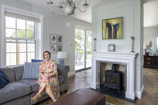 Ciara Drennan in her cosy living room, which is separated from her kitchen by the wall which houses the fireplace and stove. The floor is engineered semi-solid wood, laid in a herringbone pattern, and the wall is painted in Fleetwood pebble grey. Photo: Tony Gavin