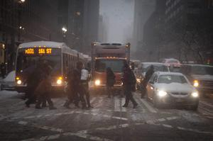 People cross a road as it snows in the Manhattan borough of New York January 26, 2015. REUTERS/Carlo Allegri