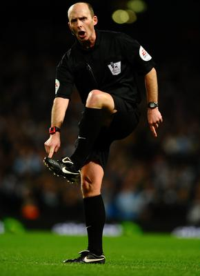 Referee Mike Dean points to his foot during the Barclays Premier League match between Manchester City and Chelsea