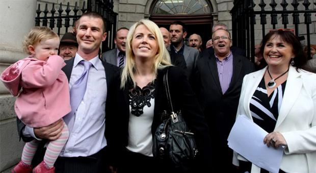 Roy and Patrice Keating, of Debt Options Ireland, with baby Eryn outside the High Court yesterday with group spokeswoman Claire Cullinane, right