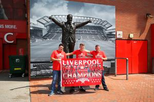 Liverpool fans pose for a photo with the Bill Shankly statue outside Anfield