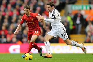 Liverpool's Joe Allen and Swansea City's Angel Rangel battle for the ball