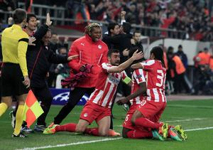 Olympiakos' Joel Campbell, center, celebrates with his teammates after scoring the second goal against Manchester United during their Champions League, round of 16, first leg soccer match at Georgios Karaiskakis stadium, in Piraeus port, near Athens, on Tuesday, Feb. 25, 2014. (AP Photo/Thanassis Stavrakis)