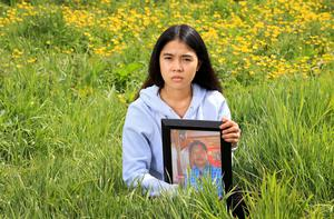 Mikee Plangca holds a photograph of her father Miguel who was a factory worker and lost his life to Covid-19, leaving Mikee, and her 3 siblings, orphans. Photo: Frank McGrath