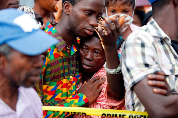 A mother who lost her son during the mudslide gets consoled near the entrance of Connaught Hospital in Freetown, Sierra Leone. Photo: REUTERS/Afolabi Sotunde