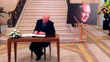 Foreign Affairs Minister Charlie Flanagan signs a book of condolences in Belfast. Photo: David Young/PA Wire