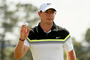 Rory McIlroy waves to the crowd as he finishes out the 18th hole during first round play of the Masters