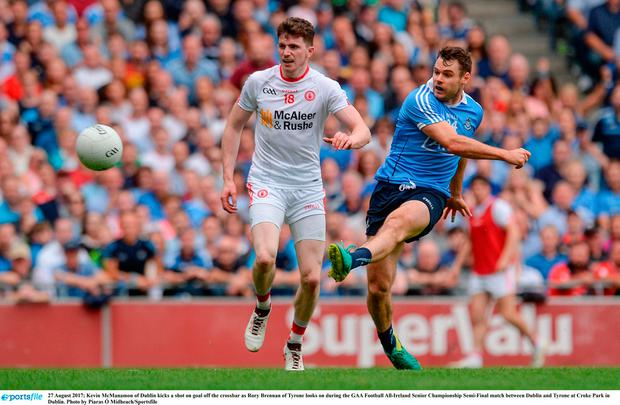 Kevin McManamon of Dublin kicks a shot on goal off the crossbar as Rory Brennan of Tyrone looks on