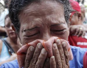 A supporter of Venezuela's President Hugo Chavez cries as she learns that Chavez has died through an announcement by the vice president in Caracas, Venezuela, Tuesday, March 5, 2013. Venezuela's Vice President Nicolas Maduro announced that Chavez died on Tuesday at age 58 after a nearly two-year bout with cancer. During more than 14 years in office, Chavez routinely challenged the status quo at home and internationally. He polarized Venezuelans with his confrontational and domineering style, yet was also a masterful communicator and strategist who tapped into Venezuelan nationalism to win broad support, particularly among the poor. (AP Photo/Ariana Cubillos)