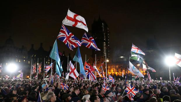 People wave the British Union Jack and England flags as they celebrate in Parliament Square on Brexit day in London, Britain January 31, 2020. REUTERS/Simon Dawson