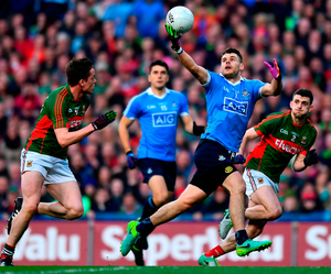 Kevin McManamon attempts to get away from Mayo duo Stephen Coen, left, and Brendan Harrison. Photo: Brendan Moran/Sportsfile