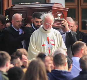 Mourners look on as the coffin of Vincent Parsons is carried out of the church
