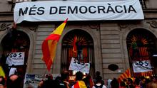 """People try to take down a banner reading """"More democracy"""" during a demonstration against independence in Catalonia"""