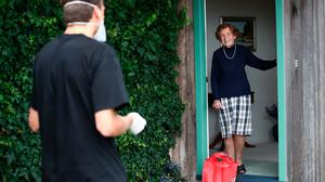 Lana Peat of East Tamaki chats to student Rupert Stobo as he delivers her groceries in Auckland, New Zealand. (Photo by Fiona Goodall/Getty Images)