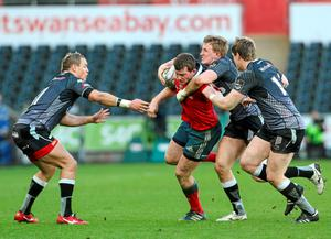 Denis Hurley is tackled and dispossessed by Ospreys players Hanno Dirksen, Ben John and Jonathan Spratt.