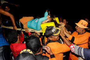 An Indonesian rescue team evacuates a Japanese tourist after she was found alive on a reef in Sanur