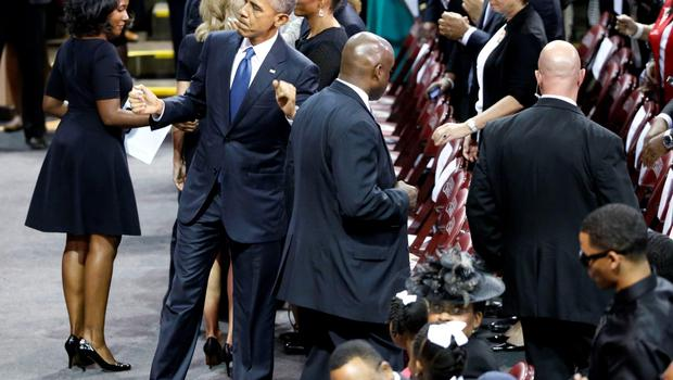 U.S. President Barack Obama dances to the gospel choir as he and first lady Michelle Obama take their seats before Obama delivered the eulogy honoring Clementa Pinckney, a pastor and state lawmaker killed in last week's church shooting in Charleston, during funeral services in Charleston, South Carolina June 26, 2015. Pinckney was among the nine people who died when a gunman opened fire in the mass shooting during bible study at Emanuel African Methodist Episcopal Church. REUTERS/Jonathan Ernst