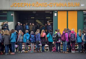 School children watch the candles placed in front of their school as they arrive at the Joseph-Koenig Gymnasium in Haltern, western Germany, Wednesday, March 25, 2015, the day after 16 school children and 2 teachers died in the Germanwings jet airliner crash in the French Alps from Barcelona to Duesseldorf. (AP Photo/Martin Meissner)