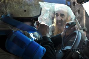 A man looks at a United Nations (UN) staff member ahead of being evacuated from the besieged district of the central Syrian city of Homs to a safer location, on February 9, 2014.
