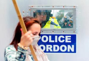 A police officer looks at demonstrators through a window in a security screen during the NATO summit in Wales