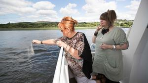 Brendan Grace's wife Eileen and daughter Amanda scattering some of Brendan's ashes near his home in Killaloe-Ballina on Saturday. Photograph by Eamon Ward