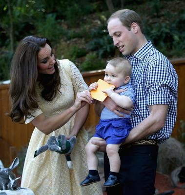 Prince William, Duke of Cambridge holds  Prince George of Cambridge as Catherine, Duchess of Cambridge gives him a commemorative card during a visit to the Bilby Enclosure at Taronga Zoo