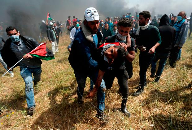 A wounded Palestinian demonstrator is evacuated during clashes with Israeli troops at the Israel-Gaza border in the southern Gaza Strip yesterday. Photo: Reuters/Ibraheem Abu Mustafa