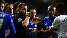 Referee Phil Dowd is surrounded by players after a late challenge from Cesc Fabregas on Jan Vertonghen.