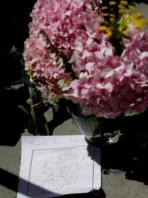 Flowers and a map of Ireland are left at a makeshift memorial for victims of a balcony that collapsed in Berkeley, Calif., Tuesday, June 16, 2015. (AP Photo/Jeff Chiu)