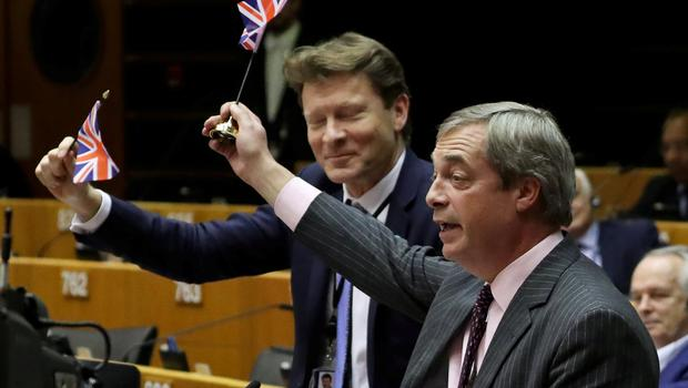 Brexit Party leader Nigel Farage along with other MEPs wave British flags ahead of a vote on the Withdrawal Agreement at the European Parliament in Brussels, Belgium January 29, 2020. REUTERS/Yves Herman