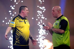 Dave Chisnall, (left) celebrates defeating Michael van  Gerwen during day fourteen of the William Hill World Darts Championship at Alexandra Palace, London.