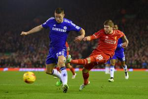 Liverpool full-back Alberto Moreno gets his shot away despite pressure from Chelsea's Gary Cahill during their Capital One Cup semi-final clash at Anfield. Photo: Michael Regan/Getty Images