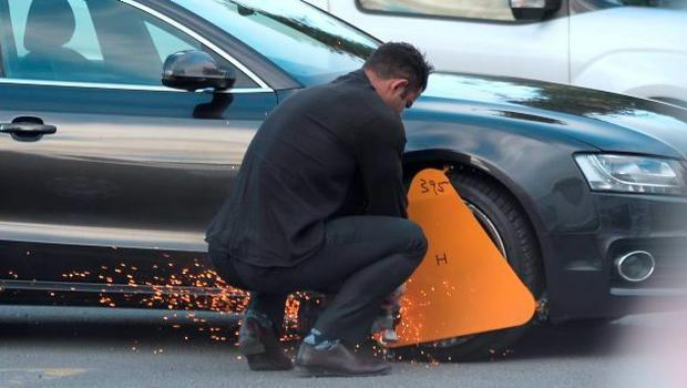 Sparks fly as the man takes an angle grinder to the clamp