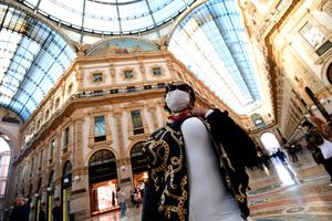 A tourist wearing a protective face mask poses for a photograph in Galleria Vittorio Emanuele II in the centre of Milan yesterday. Photo: Miguel Medina