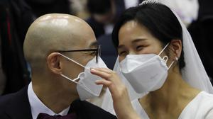 Couples used face masks during the mass wedding (Ahn Young-joon/AP)