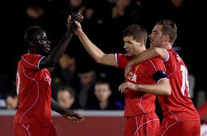 Steven Gerrard of Liverpool is congratulated by teammates Mamadou Sakho (L) and Jordan Henderson (R) after scoring his team's second goal from a free kick