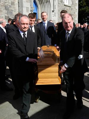 Sons Seán and Ciarán Haughey accompany the coffin as it leaves St Sylvester's Church in Malahide Photo: Damien Eagers