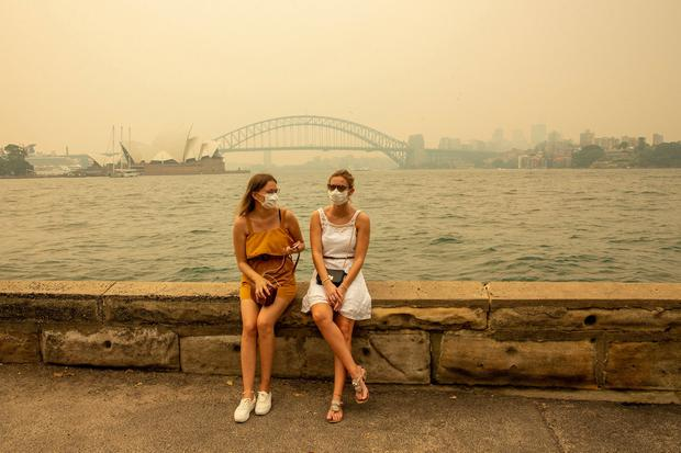 German tourists Julia Wasmiller (L) and Jessica Pryor look on at Mrs Macquarie's chair, wearing face masks due to heavy smoke on December 19, 2019 in Sydney, Australia.(Photo by Jenny Evans/Getty Images)