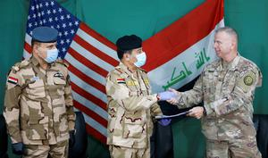 New era: US General Vincent Barker, right, with Iraqi General Mohammed Fadel, centre, during the handover of Qayyarah Airfield West. Photo: Reuters/Thaier Al-Sudani/File Photo