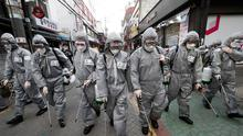 South Korean army soldiers wearing protective gears spray disinfectant as a precaution against the new coronavirus at a shopping street in Seoul, South Korea. (AP Photo/Ahn Young-joon)
