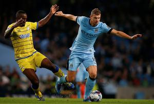 Manchester City forward Edin Dzeko is breaks away from Sheffield Wednesday's Kamil Zayatte during the Capital One Cup game at the Etihad. Photo: REUTERS/Andrew Yates