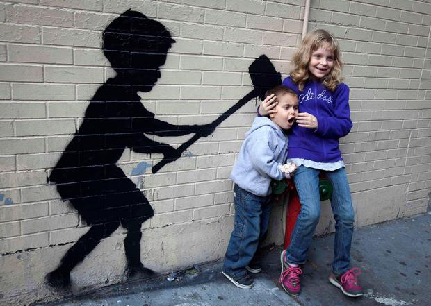 Children pose for their parents photo with a new installation of British graffiti artist Banksy's art