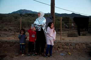 A Syrian woman covered with a thermal blanket stands with her children  after they arrive with others from Turkey, to the island of Lesbos, Greece, on Saturday, Sept. 19, 2015. (AP Photo/Petros Giannakouris)
