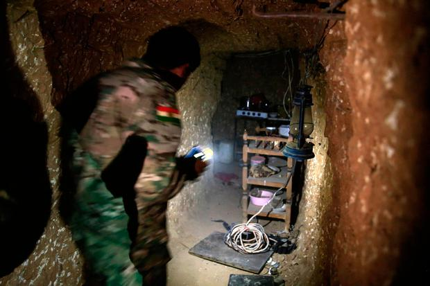 A peshmerga fighter walks through the kitchen of an underground tunnel made by Islamic State fighters. The Kurdish forces found the tunnel in the town of Badana that was liberated from the Islamic State group on Monday. Photo: AP