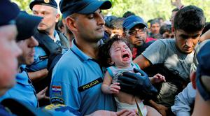 A Croatian policeman holds a crying baby as he stands among migrants waiting to board a bus in Tovarnik, Croatia, September 17, 2015.  REUTERS/Antonio Bronic