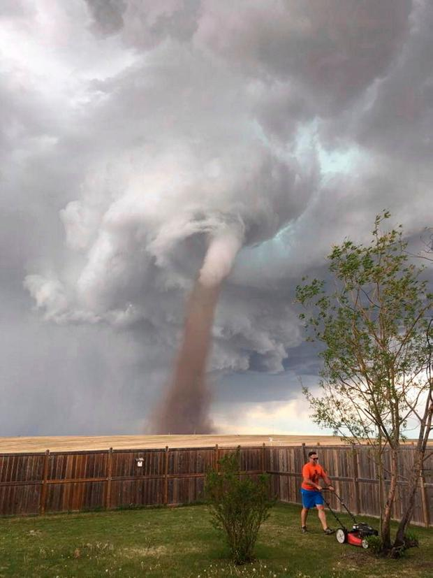 Theunis Wessels mowing his lawn in Alberta, Canada, with the huge tornado in the background. Photo: Cecilia Wessels/The Canadian Press via AP